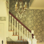 Staircase with chandelier and patterned wallpaper