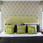 bed with decorative green pillows and green headboard with pattern wallpaper behind it