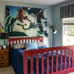 View of bed in childrens' room with hockey mural over bed